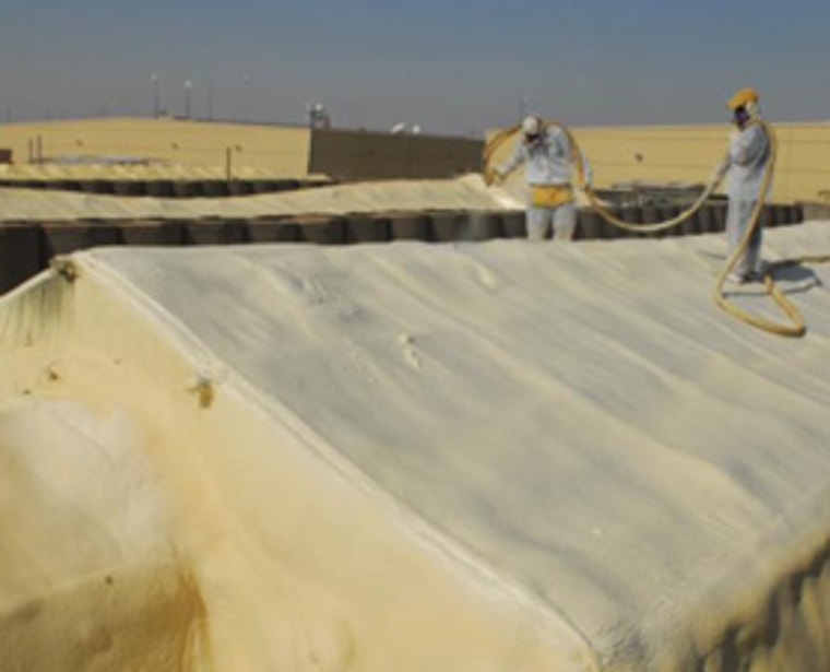 A U.S. soldier and Iraqi worker apply Terra Strong spray foam on the roof of a medical tent in Basra, Iraq.