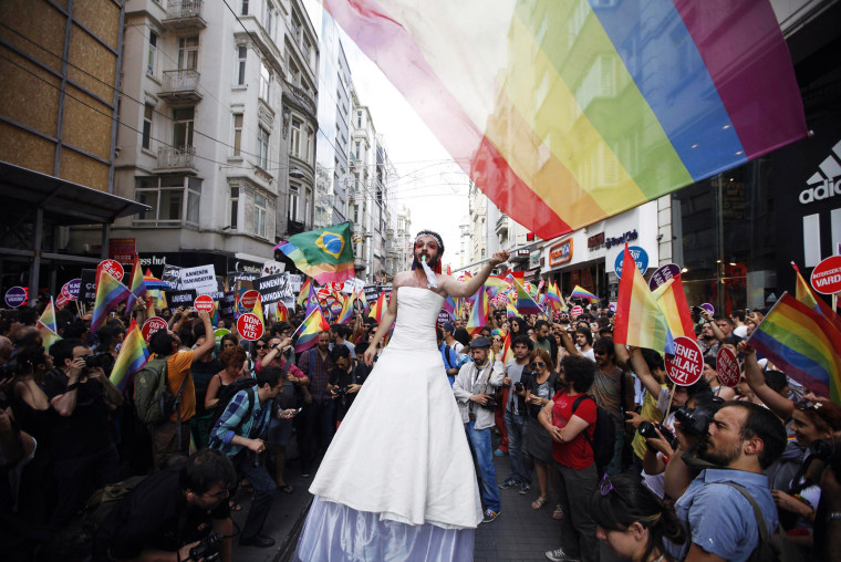 Image: A participant wears a bridal dress as he waves the rainbow flag during a gay pride parade in central Istanbul