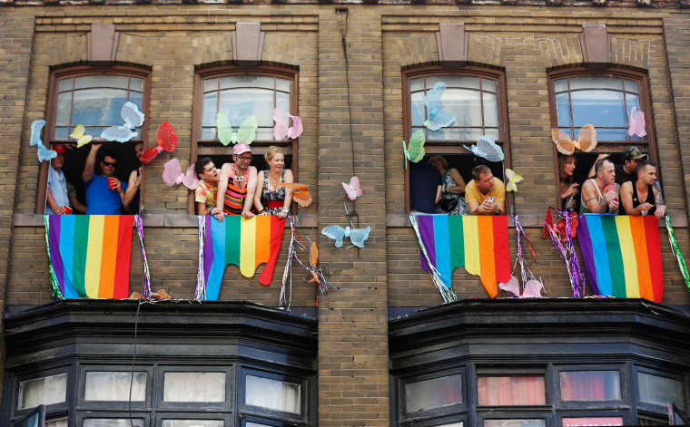 """Image: People watch from windows during the"""" WorldPride"""" gay pride Parade in Toronto"""