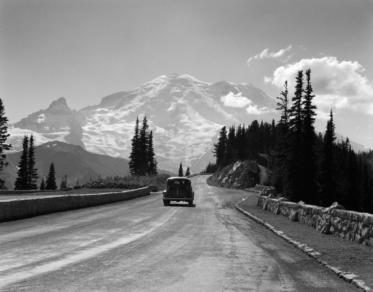 1930s SEDAN AUTOMOBILE DRIVING HIGH MOUNTAIN ROAD TOWARDS SNOW CAPPED MOUNT RAINIER WASHINGTON STATE USA. H. ARMSTRONG ROBERTS/CLASSICSTOCK/Everett Collection (m5780)