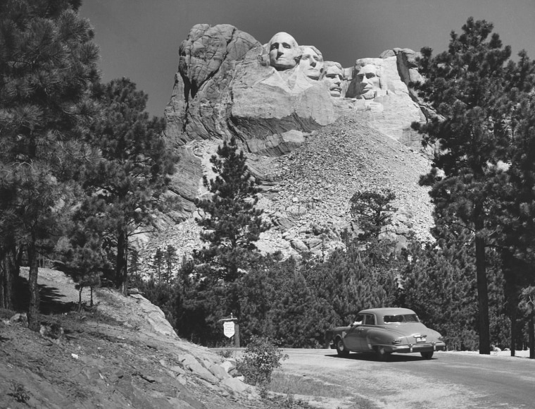 Car moving on a road past Mount Rushmore Black Hills South Dakota USA. Photo by: Superstock/Everett Collection(255-29309)
