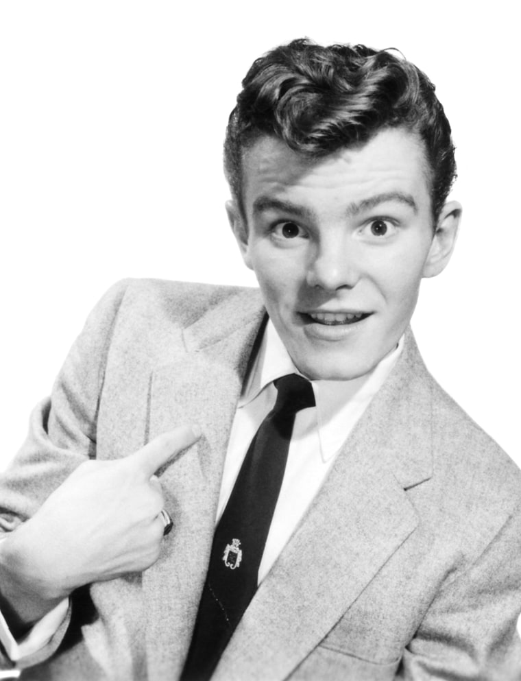 1950s YOUNG TEENAGE MAN WEARING SUIT TIE POINTING TO HIMSELF QUIZZICAL EXPRESSION POMPADOUR HAIRSTYLE LOOKING AT CAMERA - 01/01/1954 - Photo by: COLEMAN/H. Roberts Armstrong/Classicstock/Everett Collection (p1819)