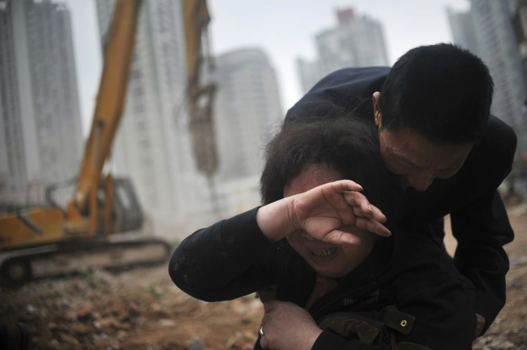 Image: Huang Sufang wipes her tears with her relative holding onto her after a part of her house was taken down by demolition workers at Yangji village in central Guangzhou city