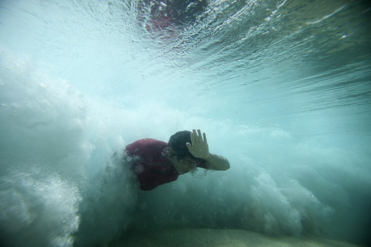 Image: A bodysurfer punches through a wave at the Ehukai sandbar near the surf break known as 'Pipeline' on the North Shore of Oahu, Hawaii.