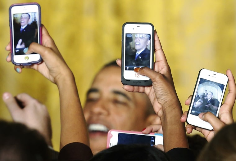 Image: Attendees photograph U.S. President Obama with their phones at a Women's History Month reception in Washington