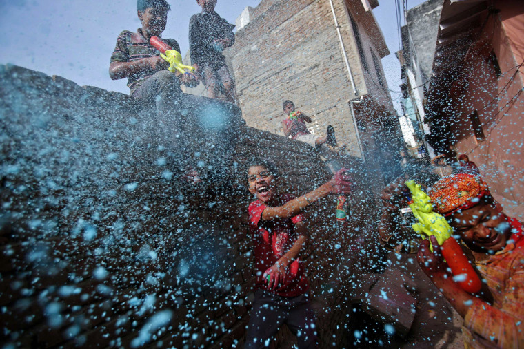 Image: Boy sprays coloured foam during Holi celebrations in a lane near the Bankey Bihari temple in Vrindavan