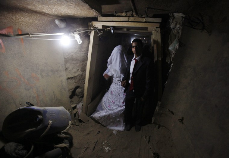 Image: Palestinian groom Emad al-Malalha walks with Manal Abu Shanar his Egyptian bride inside a smuggling tunnel beneath the Gaza-Egypt border in the southern Gaza Strip