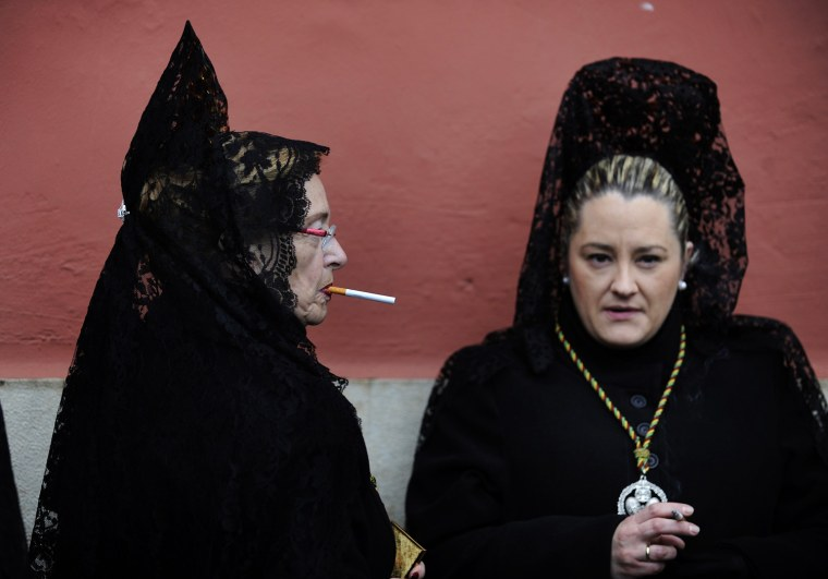 "Image: Women wearing traditional mantilla dresses smoke outside a church before taking part in the Brotherhood procession of ""Los Estudiantes"" in Oviedo"