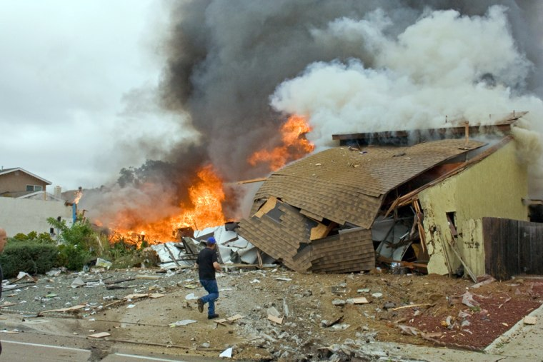 Man walks past burning debris after a military jet crashed into homes in San Diego