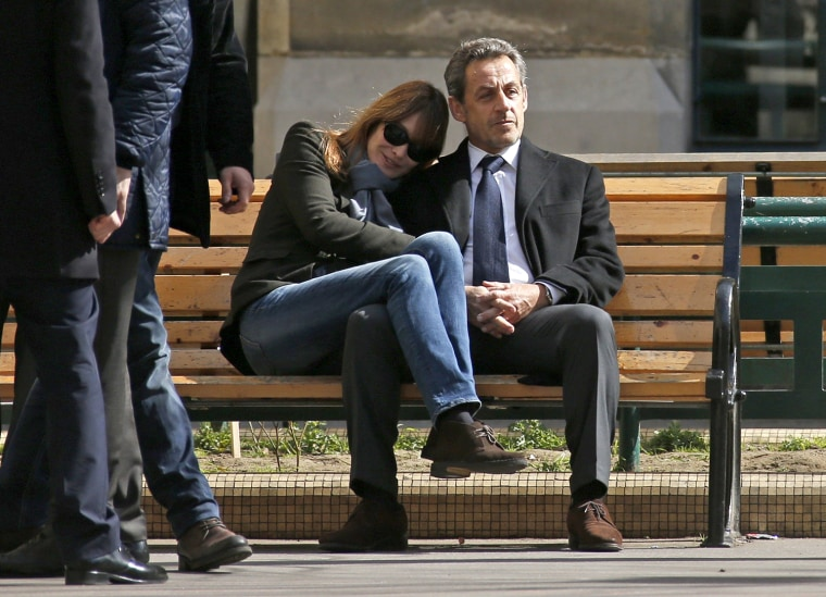 Image: Former French President Nicolas Sarkozy sits on a bench with his wife and singer Carla Bruni-Sarkozy after voting at a polling station in the first round in the French mayoral elections in Paris