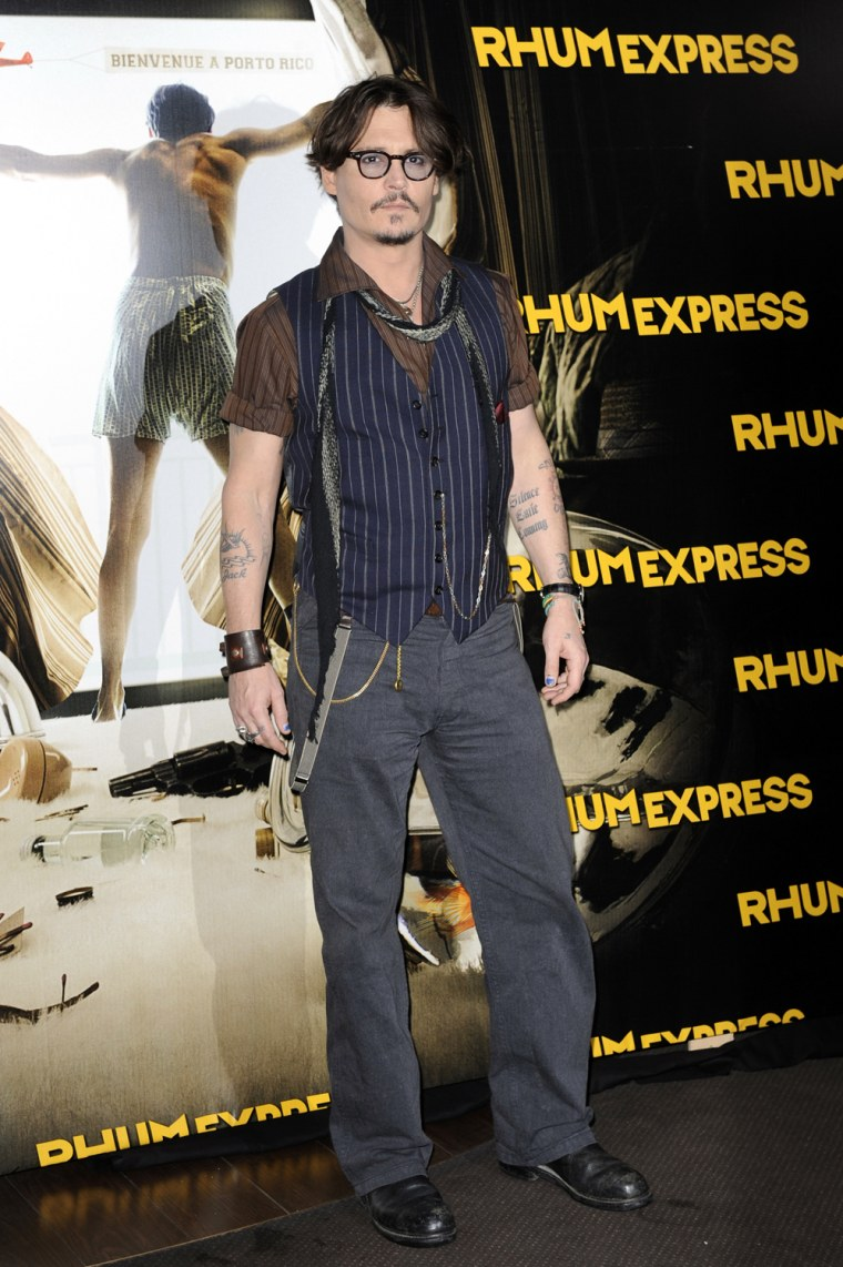 """Image: Actor Depp poses for photographers as he arrives for the premiere of the film """"The Rum Diary"""" in Paris"""