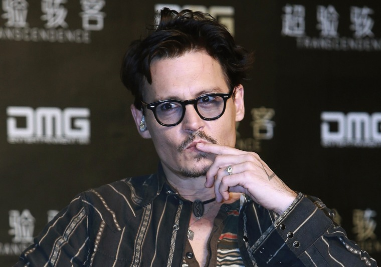 """Image: Actor Depp gestures during a promotional event of his new movie """"Transcendence"""", on his first visit to China in Beijing"""