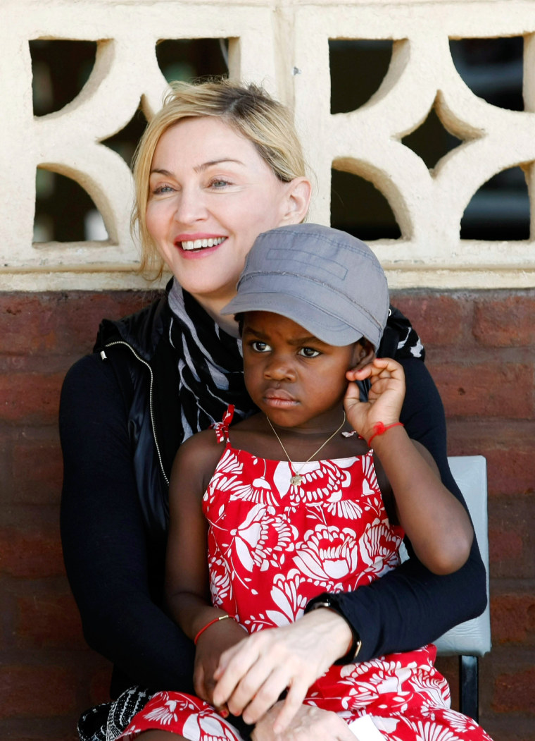 Image: U.S. pop star Madonna holds her adopted Malawian child Mercy James during a visit to Gumulira village