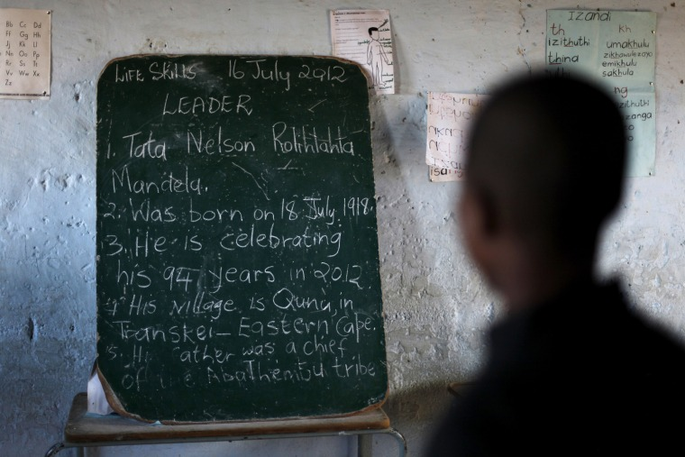 Image: School children read the history of former South African President Nelson Mandela written on a chalkboard, ahead of the opening of a container library by the Bill Clinton foundation in celebration of Mandela day, at a school in Qunu