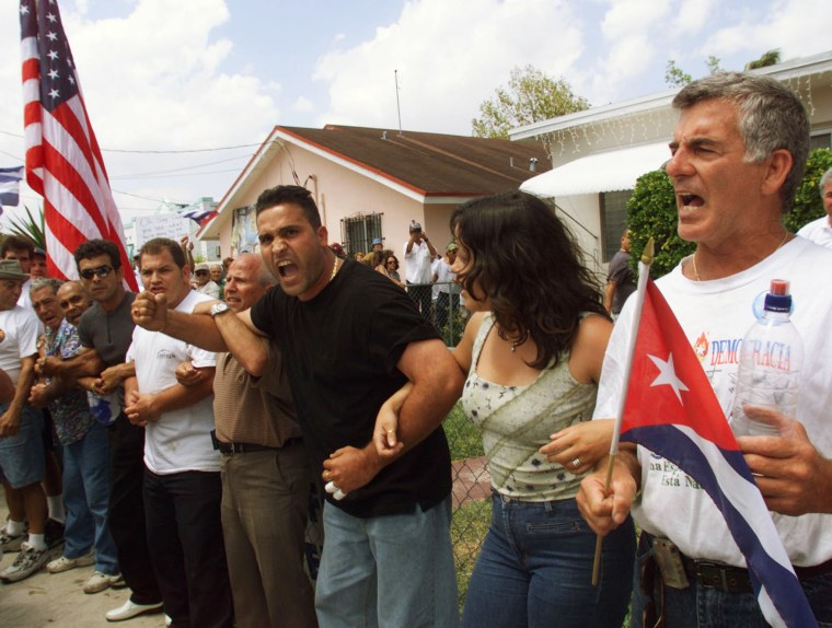 Image: PROTESTORS LINK ARMS IN FRONT OF ELIAN GONZALEZ FLORIDA HOME.