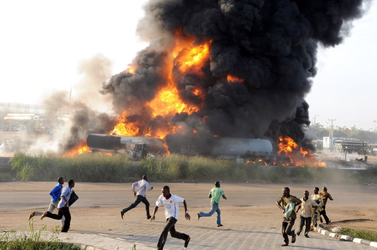 Image: Pedestrians run from the scene of a fire ravaging four fuel tankers on Lagos' Ibadan highway on May 11.