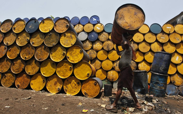 Image: A labourer carries an empty oil container at a wholesale fuel market in Kolkata