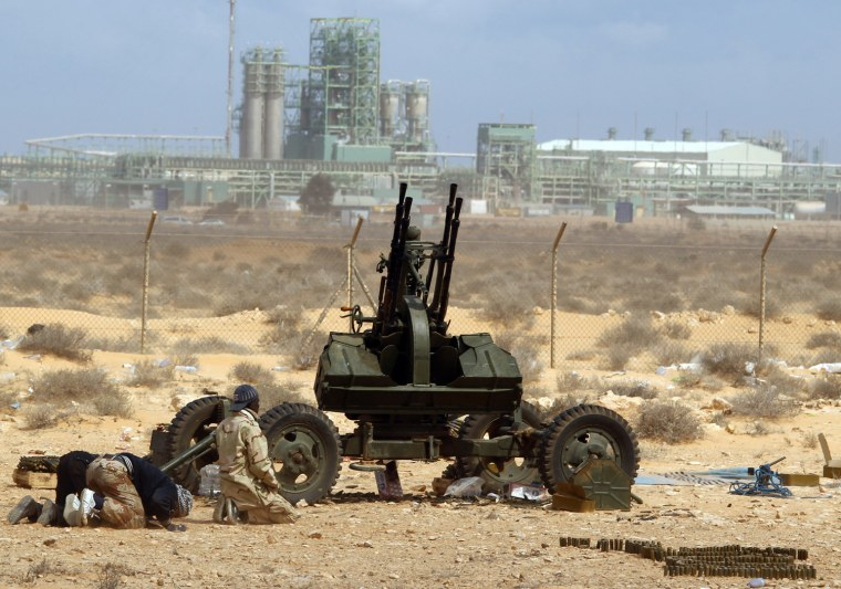 Image: Rebels pray in front of anti-aircraft gun in front of a refinery in Ras Lanuf
