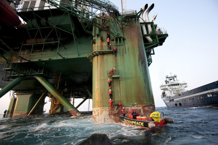 Image: Greenpeace activists climb ladders on the Leiv Eiriksson drilling rig operated by British oil explorer Cairn Energy