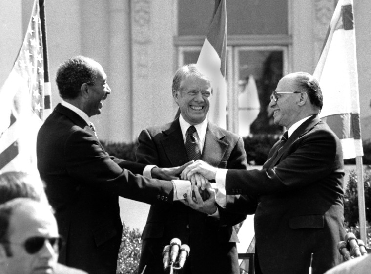 Egyptian President Anwar Sadat, left, U.S. President Jimmy Carter, center,  and Israeli Prime Minister Menachem Begin clasp hands on the north lawn of the White House after signing the peace treaty between Egypt and Israel on March 26, 1979. Sadat and Begin were awarded the Nobel Peace Prize for accomplishing peace negotiations in 1978. The rest of the Arab world shunned Sadat, condemning his initiative for peace. President Carter was pivotol for the two leaders to meet at Camp David and as a result, peace began between Arabs and Jews. (AP Photo/ Bob Daugherty)