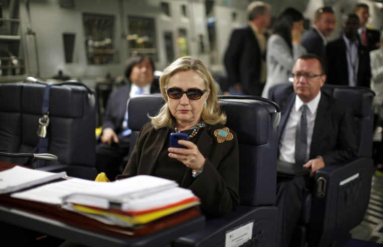 Image: U.S. Secretary of State Hillary Clinton checks her PDA upon her departure in a military C-17 plane from Malta bound for Tripoli,  Libya