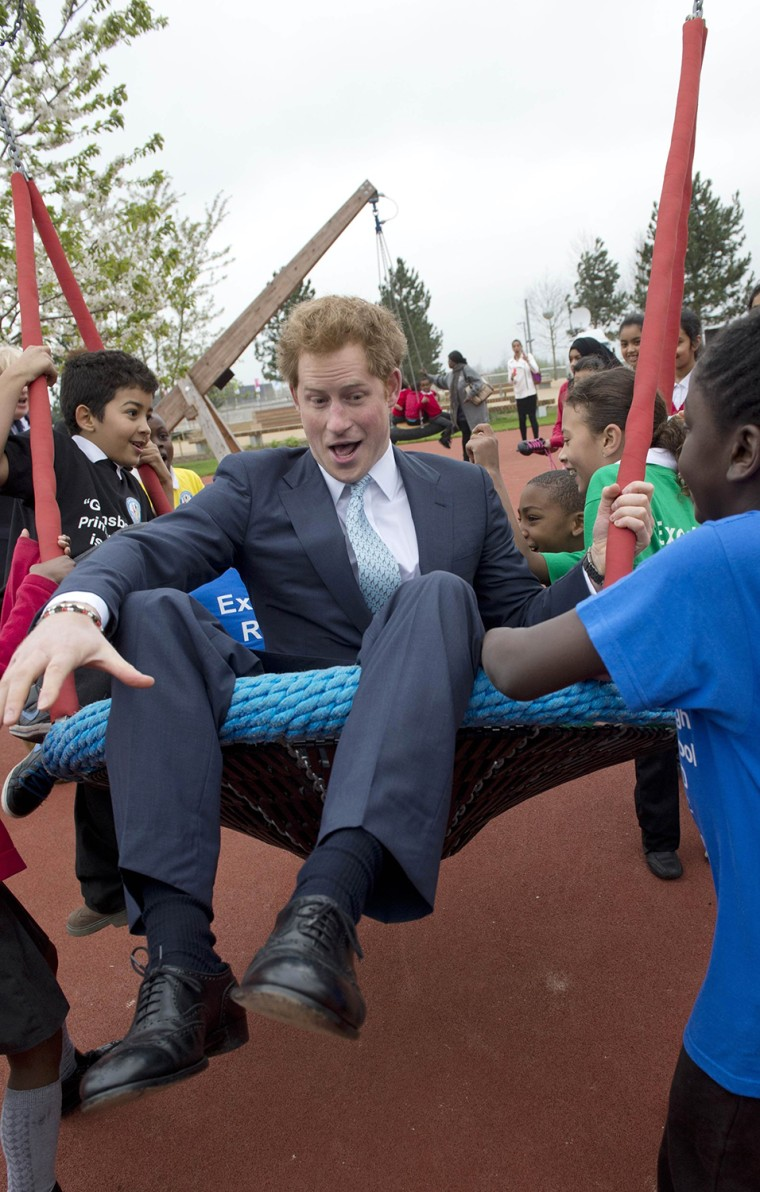 Image: Britain's Prince Harry plays on a swing with children during a tour of the Queen Elizabeth Olympic Park ahead of its public opening tomorrow at Stratford in east London