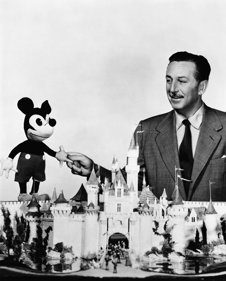 Image: Walt Disney shaking hands with Mickey Mouse doll behind scale model of the Sleeping Beauty Castle en