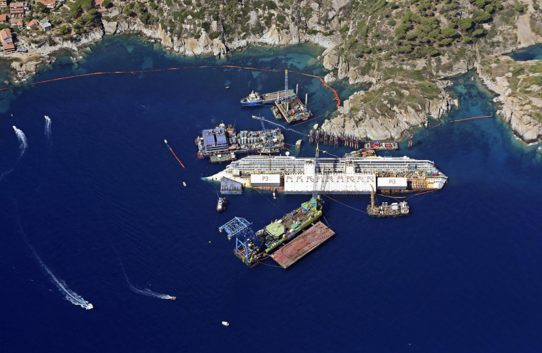Image: An aerial view shows the Costa Concordia as it lies on its side next to Giglio Island taken from an Italian navy helicopter
