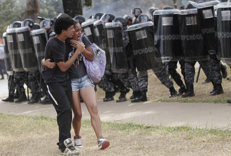 Image: A couple runs near riot police near Mane Garrincha Stadium before the international friendly soccer match in Brasilia