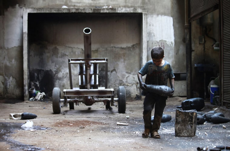 Image: Issa carries a mortar shell in a weapons factory of the Free Syrian Army in Aleppo