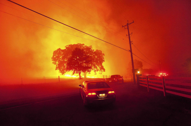Image: Residents flee as winds whip flames from the Morgan fire along Morgan Territory Road near Clayton, California