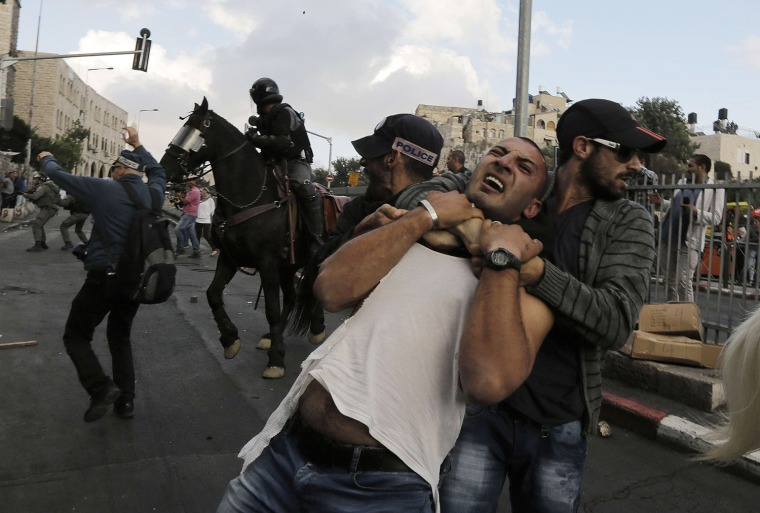 Image: An undercover Israeli policeman detains a Palestinian protester during clashes in Jerusalem's Old City