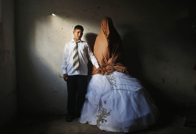 Image: Palestinian groom Ahmed Soboh and his bride Tala stand inside Tala's house which damaged during Israeli strike in 2009, during wedding party in Beit Lahiya