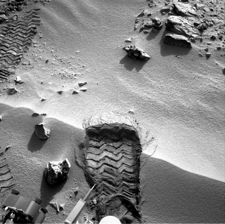 """Image: Handout of NASA's Mars rover Curiosity cut a whell scuff mark into a wind-formed ripple at the """"rocknest"""" site"""