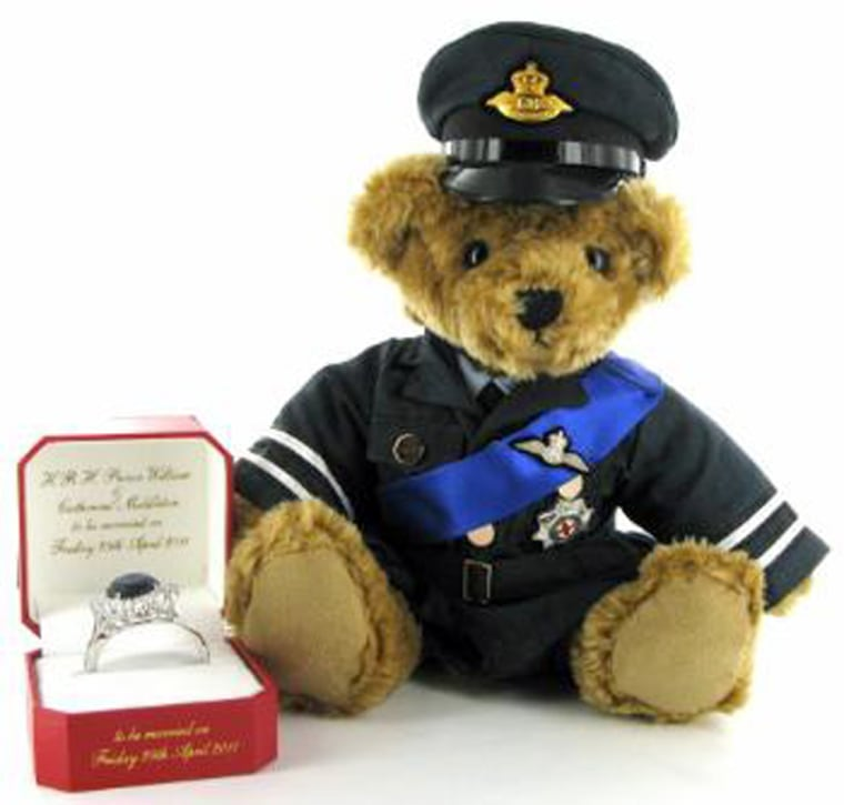 Royal Wedding Teddy Meet William our The Royal Wedding Teddy Bear, from The Great British Bear Company Surely our most enchanting Royal Wedding Collectable of all! Beautifully dressed in full Royal Air Force Uniform and complete with a replica Engagement Ring. William is Limited to an edition of just 5,000. William stands 30 cms tall.    Our Great British H.R.H William Teddy Bear is dressed in a Royal 'Bear Force' dress uniform. The peaked cap is made from authentic air force blue fabric and displays the golden die caste Royal Bear force wings. William's Dress jacket has the double black and silver armbands on each sleeve signifying his rank of flight lieutenant. The high polished brass buttons and authentic pressed pleated pockets make his little jacket look just like the real thing. William proudly wears his Royal blue sash and silver wings above the Silver Star honour, reserved for serving royalty. William is not empty handed.... On his lap he holds a red leather ring box beautifully embossed with gold line work and the words: 'H.R.H Prince William & Catherine Middleton To be married on Friday 29th April 2011'. Inside this beautifully lined box is a replica of Diana's (now Kate's) famous ring. The ring is made to fit our Great British Teddy Bear and is 44mm in diameter. This famous cluster ring has split shoulders and is plated in white gold. Sixteen 5mm brilliant cut white zircon stones surround a 21mm Oval Brilliant cut blue zircon. We have even engraved the inside of the ring with the words H.R.H Prince William & Catherine Middleton. The inside of the box is also embossed with 'H.R.H Prince William & Catherine Middleton To be married on Friday 29th April 2011'. Each bear comes with a numbered commemorative certificate of authentication.