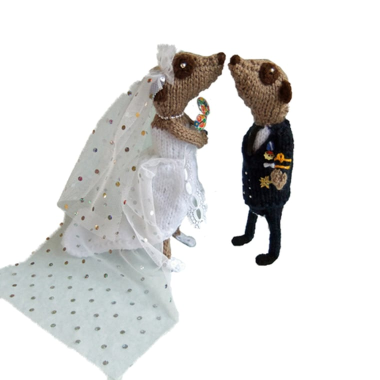 """Royal Wedding Meerkats Prince William and Kate in their marriage finery £53.00 Well what can I say? They *had* to be meerkatted, but of course we don't yet know what they'll wear.   I've made two versions of the Groom, one in RAF, one in Navy - choose your favourite, or ask me to knit a different uniform (he can also wear Army and Guards)   For Kate, I've gone with white, off-the-shoulder and long train. Her second-hand engagement ring is on show, and to keep in tune with our dreadful economy she is carrying a simple posy of wild flowers.   If you have a better idea for the bridal wear, feel free to commission your own version!   Not suitable for small children due to wiring, each meerkat is around 7"""" tall."""