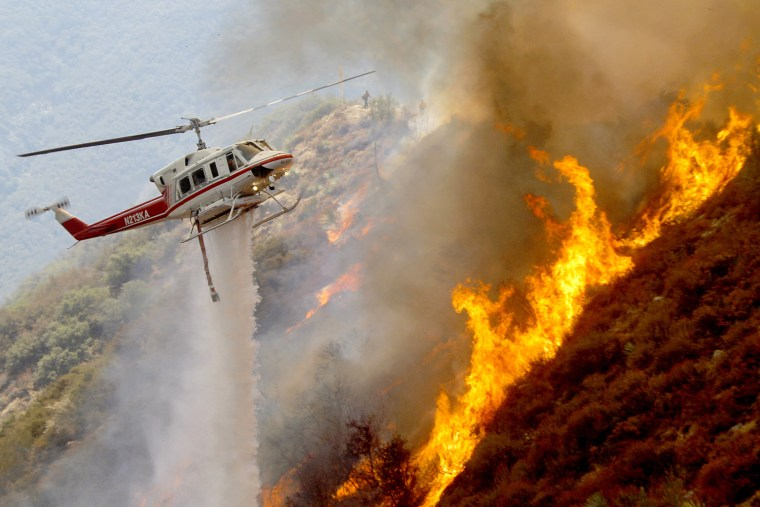 Image: A helicopter drops water on a wildfire