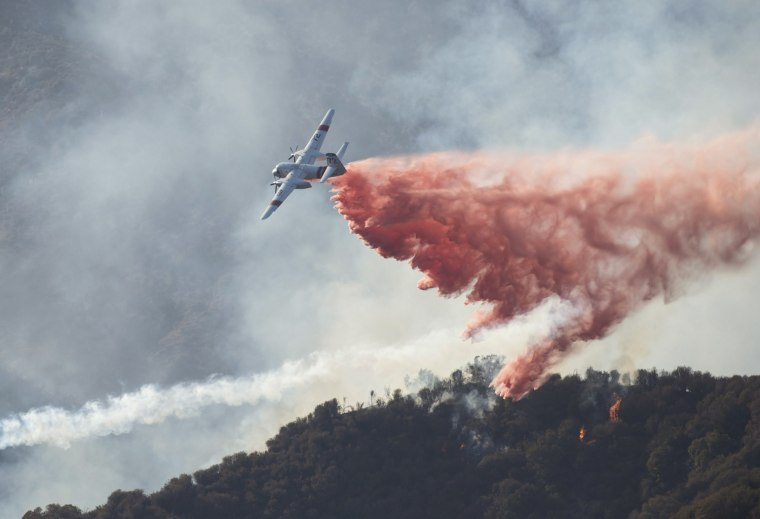 Image: A firefighting plane dropping retardant on the 3,600-acre wildfire burning in the Angeles National Forest in the San Gabriel Mountains north of Azusa, California,