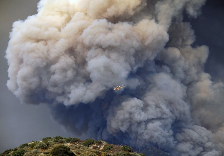 Image: A sky crane helicopter flies past a plume of thick smoke rising from the hills above San Gabriel mountains in the Angeles National Forest, California