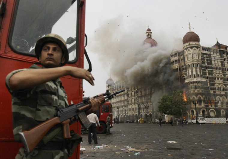 An Indian soldier takes cover as the Taj Mahal hotel burns during gun battle between Indian military and militants in Mumbai, India, on Nov. 29, 2008.
