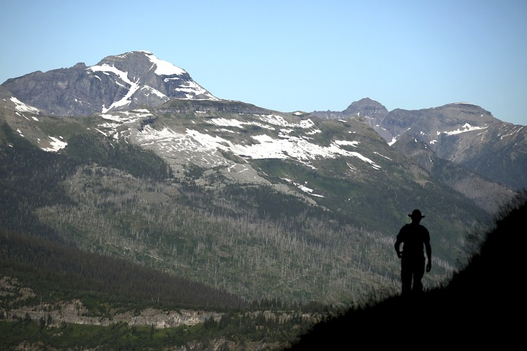 Image: Nick Wieland of Eagan, Minnesota hikes the Highline Trail with a view of Heaven's Peak in Glacier National Park, Montana