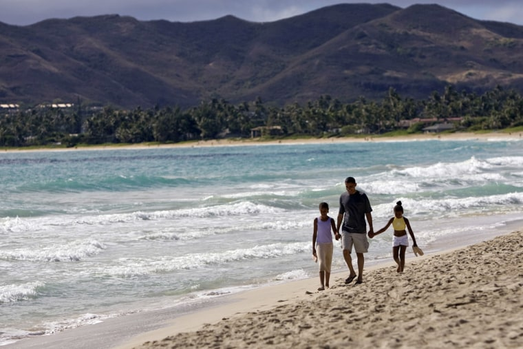 ** FILE ** In this Aug. 12, 2008 file photo President-elect Barack Obama walks the beach with his daughters Malia, 10, left, and Sasha, 7, during his vacation in Kailua, Hi. Places that U.S. presidents have called home often become major tourist attractions, from estates at Mount Vernon and Monticello, to Hodgenville, Ky., where Abe Lincoln's log cabin once stood. But if you want to see all the places connected to Obama's life story, you'd need to visit three countries, five time zones and six states. (AP Photo/Marco Garcia, File)