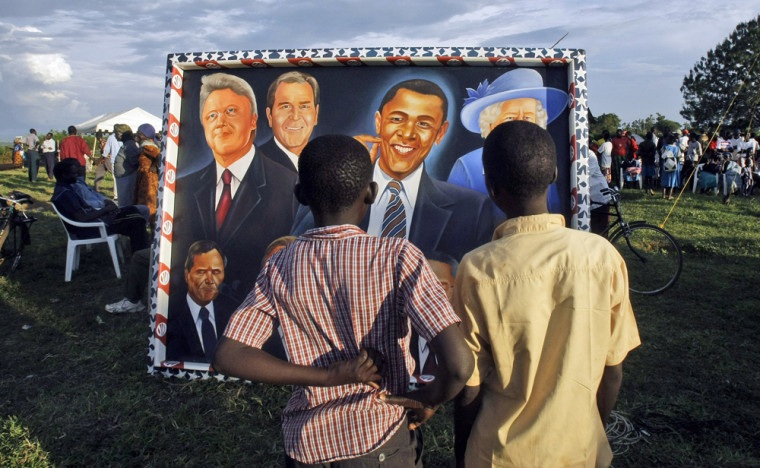** FILE ** In this Nov. 4, 2008 file photo, local boys in Kogelo village, Kenya look at a painting featuring President-elect Barack Obama, center, alongside, from left, former U.S. President Bill Clinton, current U.S. President George W. Bush and Britain's Queen Elizabeth II during a gathering of people on Nov. 4, 2008. Places that U.S. presidents have called home often become major tourist attractions, from estates at Mount Vernon and Monticello, to Hodgenville, Ky., where Abe Lincoln's log cabin once stood. But if you want to see all the places connected to Obama's life story, you'd need to visit three countries, five time zones and six states.  (AP Photo/Matt Dunham, File)