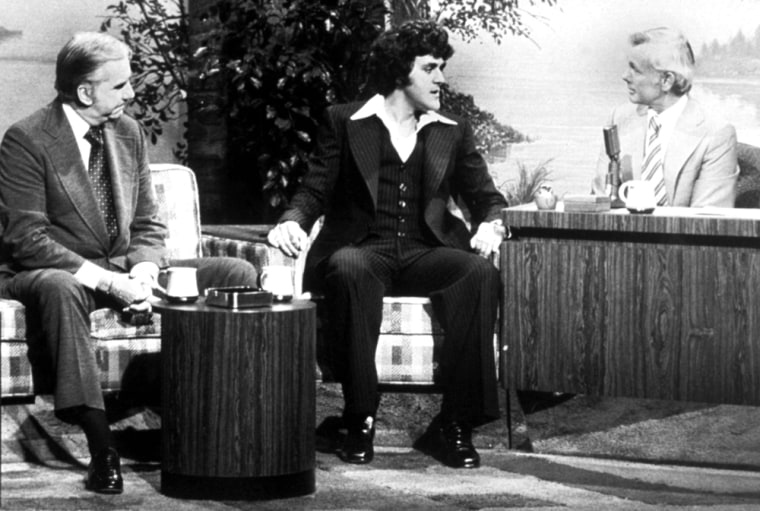 """Jay Leno made his first """"Tonight Show"""" appearance in 1977, joining host Johnny Carson, right, and Ed McMahon, left, on the couch. Leno would become Carson's regular substitute host in 1987 before taking the helm of the show in 1992."""