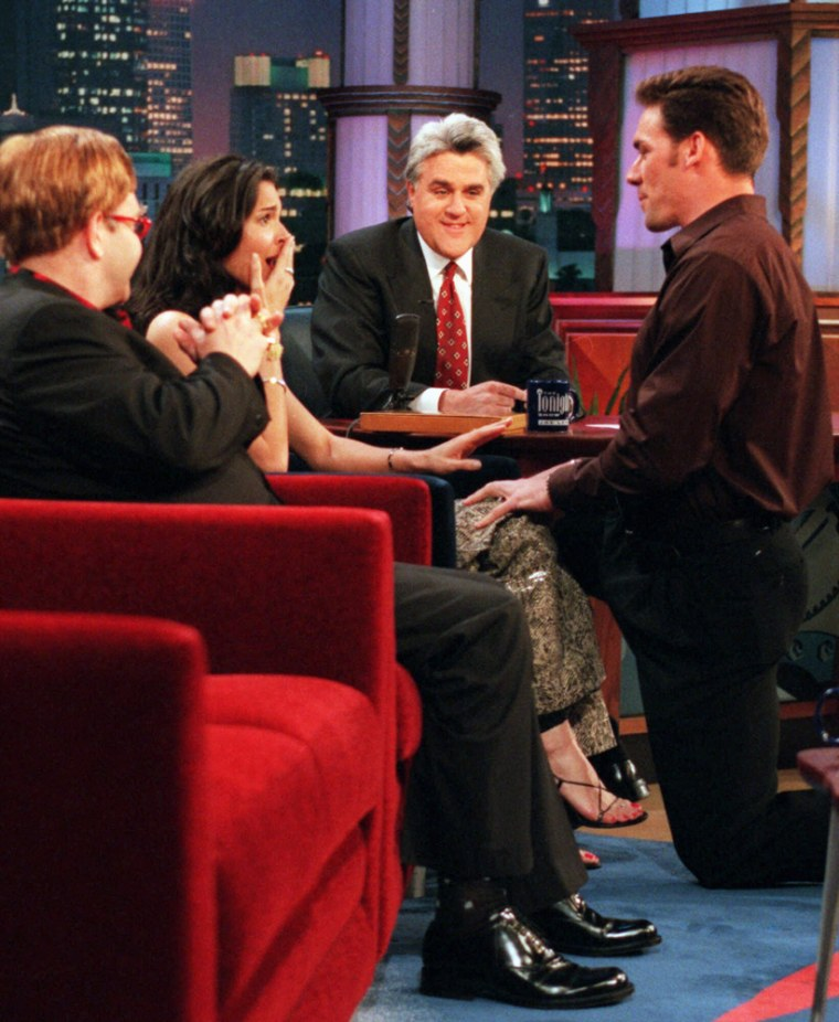 """Leno, center and singer Elton John, left, looked on while then-New York Giants defensive back Jason Sehorn surprises his girlfriend, actress Angie Harmon, with a marriage proposal during the taping of """"The Tonight Show"""" on Monday, March 13, 2000. Her answer was """"Yes."""""""