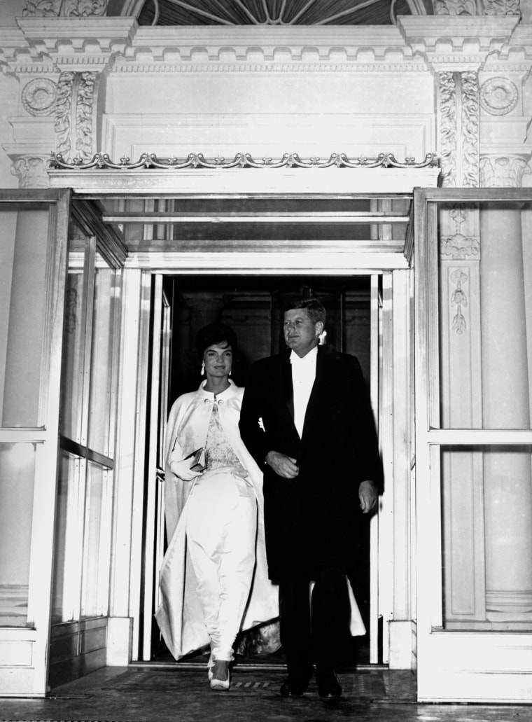 """Newly-elected President and Mrs. John F. Kennedy leave the White House, in Washington, D.C., on Jan. 20, 1961, for a series of visits to inaugural balls. The first lady wore her specially-designed haute couture white silk sheath and matching coat.  As the 35th President of the United States,  Kennedy defeated Vice President Richard  M. Nixon in one of the closest presidential elections of the 20th century by a plurality of just 114,000 votes.  The Kennedys brought a cultured and glamorous era known as """"Camelot""""  to American politics.  (AP Photo/Henry Burroughs)"""