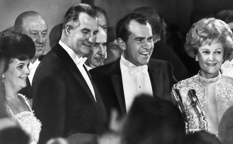 Pres. Richard Nixon, second from right, his wife First Lady Pat Nixon, right, Vice Pres. Spiro Agnew and Mrs. Judy Agnew, left, share the spotlight at one of six inaugural balls held for Pres. Nixon, Jan. 21, 1969, Washington, D.C. In background are Rep. Leslie Arends of Illinois, left, and Atty. Gen. John Mitchell, center. (AP Photo)