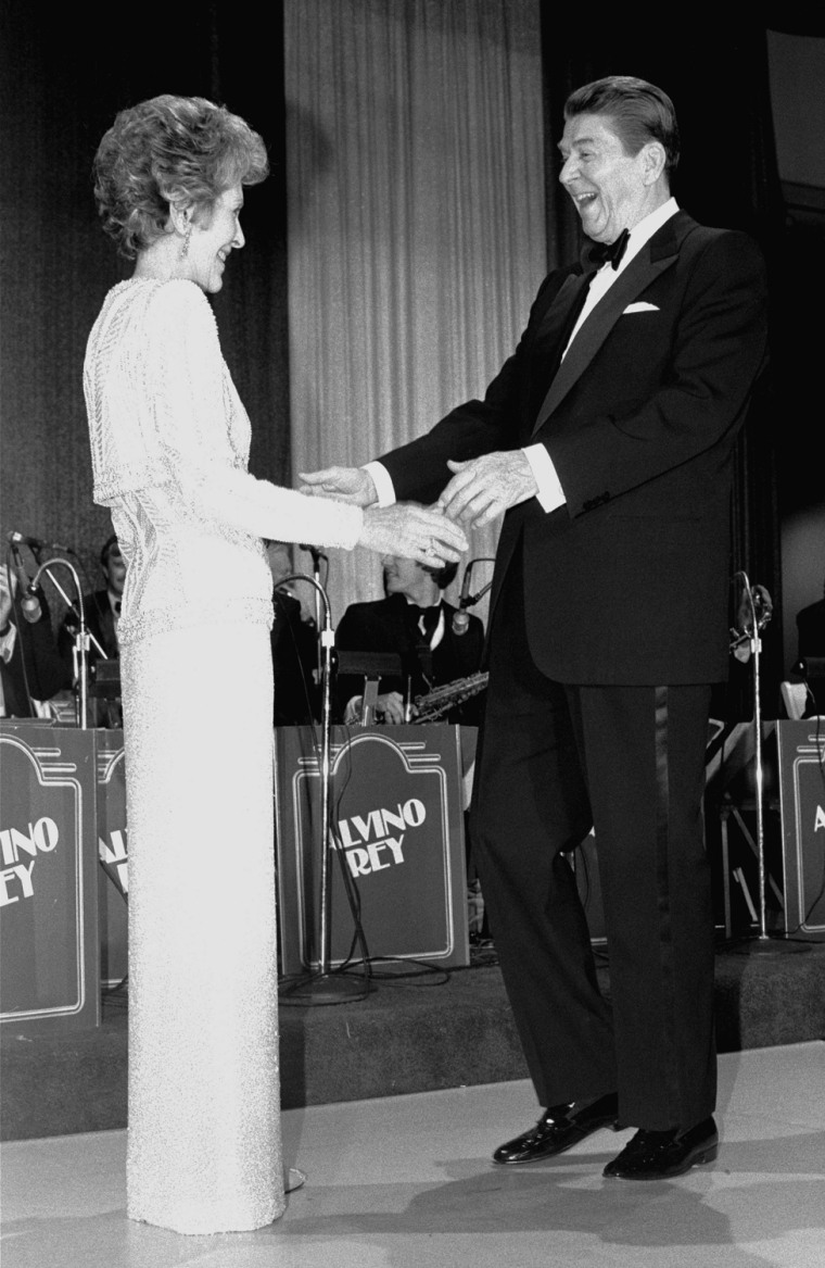 President Ronald Reagan gestures to first lady Nancy Reagan at the inaugural ball at the Smithsonian's Air and Space Museum in Washington Monday evening, January 21, 1985.  President Reagan reenacted his oath of office earlier in the day in the rotunda at the Capitol Building. (AP Photo/Ira Schwarz)