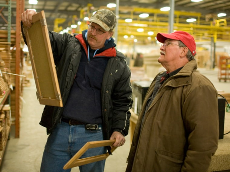 Greg Huber and Richard Eysol examine unused cabinet material that they just purchased at the auction of the Americamp RV factory.