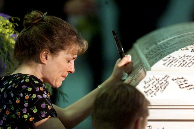 A woman cries after writing her message on the casket containing the body of Rachel Scott, at the funeral services in Littleton 24 April 1999.  Scott was one of the twelve students from Columbine High School who died following a shooting by two fellow students 20 April 1999.  (ELECTRONIC IMAGE)  AFP PHOTO/POOL/Rick WILKING